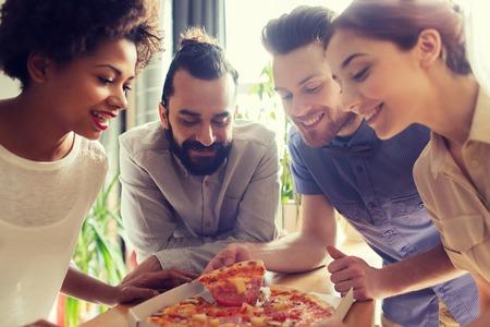 negocio, la comida, el almuerzo y la gente concepto - equipo de negocios feliz comiendo pizza en la oficina