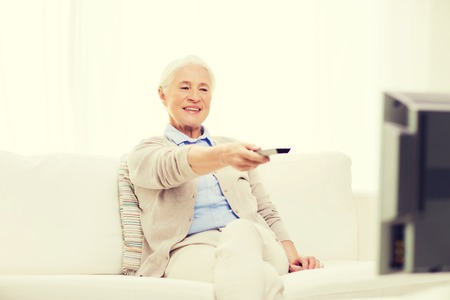 technology, television, age and people concept - happy senior woman watching tv and changing channel with remote control at home