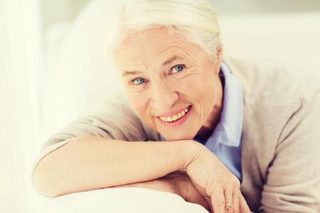 la edad y el concepto de la gente - feliz sonriente cara de la mujer mayor en su casa