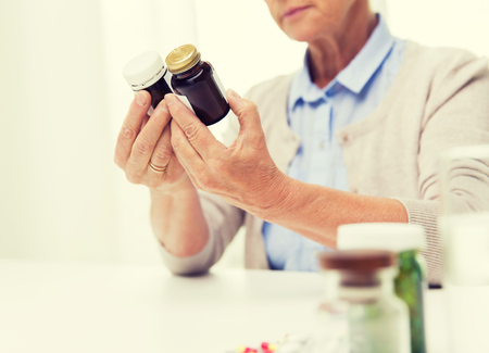 home health care: age, medicine, health care and people concept - close up of senior woman looking at jars with medicine at home or hospital office Stock Photo