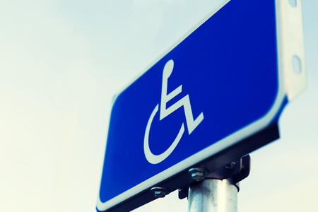 up code: traffic laws and highway code concept - close up of road sign for disabled outdoors