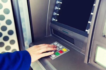 pin code: finance, technology, money and people concept - close up of hand entering pin code at cash machine