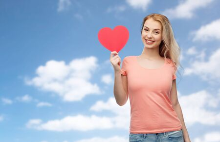 mujer enamorada: love, romance, charity, valentines day and people concept - smiling young woman or teenage girl with blank red heart shape over blue sky and clouds background