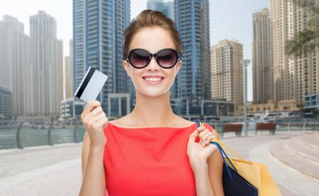 people, holidays, tourism, travel and sale concept - young happy woman with shopping bags and credit card over dubai city street background