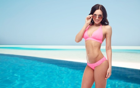 personas mirando: people, fashion, swimwear, summer and beach concept - happy young woman in sunglasses and pink swimsuit looking at you over maldives beach with swimming pool background