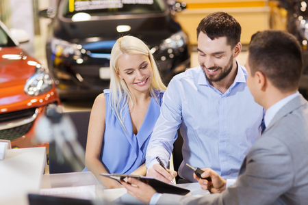 documents: auto business, sale and people concept - happy couple with dealer buying car in auto show or salon