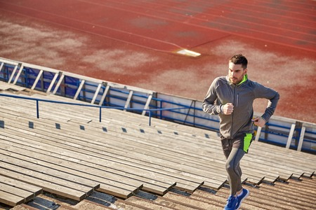 upstairs: fitness, sport, exercising and people concept - young man running upstairs on stadium Stock Photo