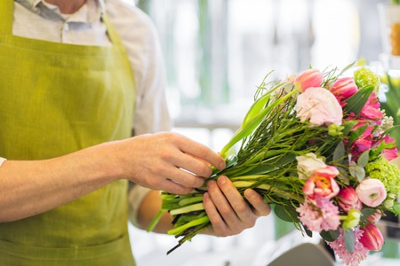 floristry: people, business, sale and floristry concept - close up of florist man making bunch at flower shop