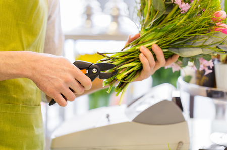 floristry: people, business, sale and floristry concept - close up of florist man making bunch and cropping stems by pruner at flower shop