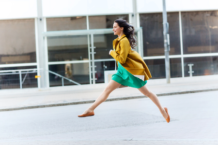 freedom concept: fashion and people concept - happy young woman or teenage girl running and jumping high on city street Stock Photo