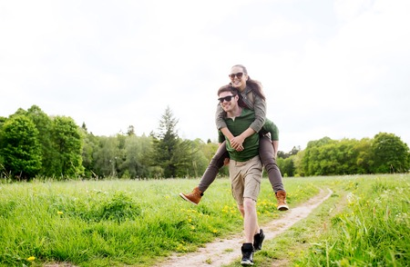 piggy back: travel, hiking, backpacking, tourism and people concept - happy couple with backpacks having fun and walking along country road outdoors