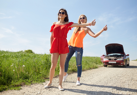 suburban street: road trip, transport, travel, gesture and people concept - young women with broken car showing hitchhiking gesture asking for help at countryside