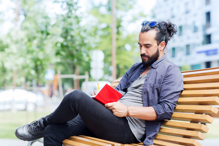 mode de vie, la créativité, la pige, l'inspiration et les gens concept - homme créatif avec bloc-notes ou d'écriture de journal assis sur la ville rue banc
