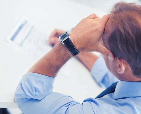 morgage: business, office, school and education concept - stressed man filling tax form