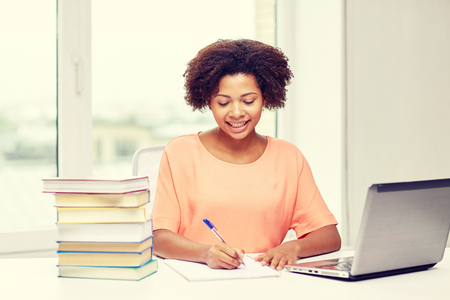 person writing: people, technology and education concept - happy african american young woman sitting at table with laptop computer and books at home