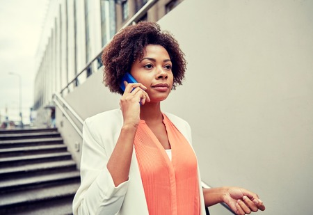 elegant staircase: business, communication, technology and people concept - young african american businesswoman calling on smartphone going down stairs into city underpass