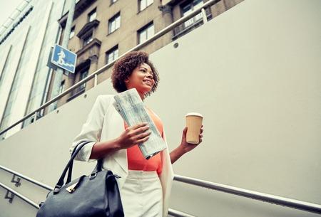 bajando escaleras: negocios y concepto de la gente - joven sonriente africano americano de negocios con la taza de caf� bajando escaleras en paso subterr�neo de la ciudad