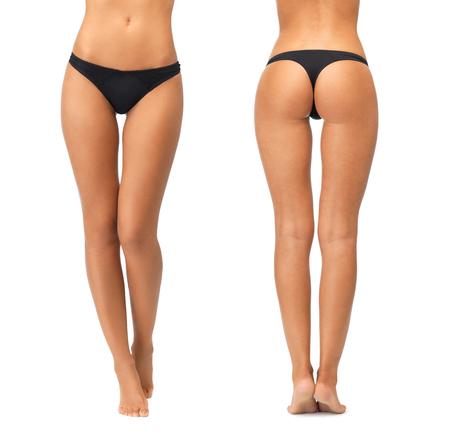 persone, bellezza, cura del corpo, biancheria intima e il concetto di dimagrimento - gambe femminili e fondo in mutandine del bikini nero su sfondo bianco