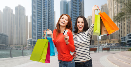 seafronts: shopping, sale, tourism and people concept - two smiling teenage girls with shopping bags and credit card over dubai city street background