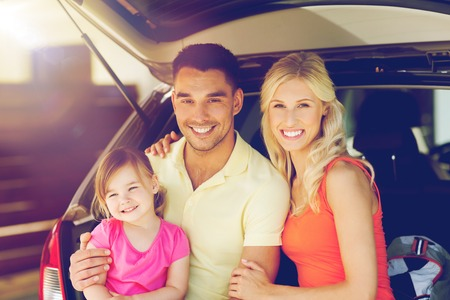 private insurance: transport, leisure, road trip and people concept - happy family with little girl sittin on open hatchback car  trunk at home parking space