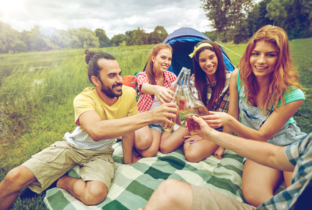 campsite: camping, travel, tourism, hike and people concept - happy friends with glass bottles drinking cider or beer at campsite