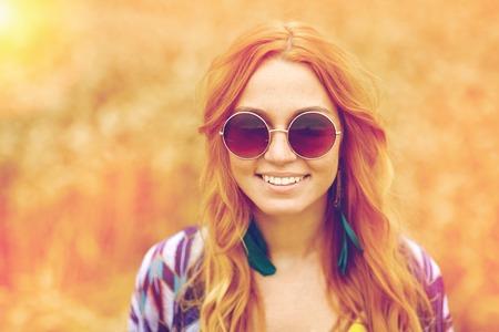 Nature, été, la culture et les gens jeunes concept - souriante jeune rousse hippie femme dans des lunettes de soleil en plein air Banque d'images - 62716810