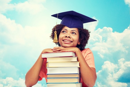 education, school, knowledge and people concept - happy smiling african american student girl in bachelor cap with books sitting at table and dreaming over blue sky and clouds background Stock Photo - 62716816