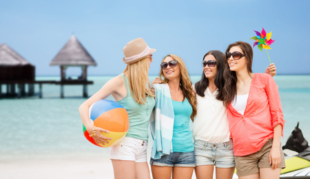 resort beach: summer holidays, vacation and beach activities concept - smiling girls in shades having fun on the beach