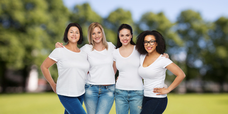 diverse: friendship, diverse, body positive and people concept - group of happy different size women in white t-shirts hugging over summer park background Stock Photo