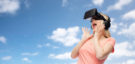 mediated: technology, virtual reality, entertainment and people concept - happy young woman with virtual reality headset or 3d glasses and headphones over blue sky and clouds background
