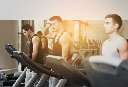 men exercising: sport, fitness, lifestyle, technology and people concept - group of men exercising on treadmill in gym