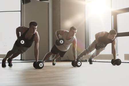 push ups: sport, fitness, lifestyle and people concept - group of men with dumbbells in gym Stock Photo