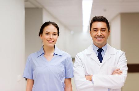 bata blanca: cuidado de la salud, profesión, las personas y concepto de la medicina - doctor sonriente en la capa blanca y la enfermera en el hospital