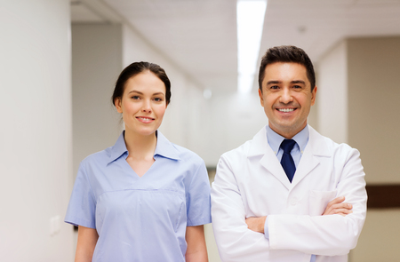 white coat: healthcare, profession, people and medicine concept - smiling doctor in white coat and nurse at hospital