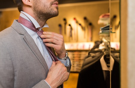 formal dressing: sale, shopping, fashion, style and people concept - close up of young man in suit choosing and tying tie and looking to mirror in mall or clothing store