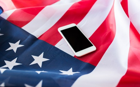 nationalism: technology, american independence day, patriotism and nationalism concept - close up of smartphone with black blank screen on american flag