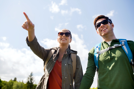 pointing: travel, hiking, backpacking, tourism and people concept - happy couple with backpacks walking outdoors and pointing finger to something Stock Photo