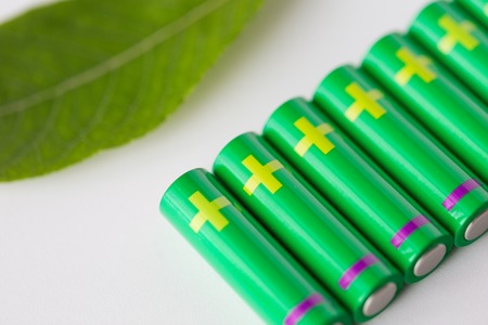 green power: recycling, energy, power, environment and ecology concept - close up of green alkaline batteries and leaf Stock Photo