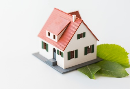 housing, environment and ecology concept - close up of living house model and green leaves Stock Photo