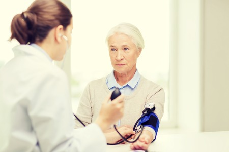 medicine, age, health care and people concept - doctor with tonometer checking senior woman blood pressure level at hospital