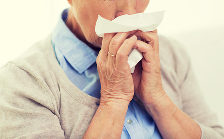 home health care: health care, flu, hygiene, age and people concept - close up of sick senior woman blowing nose to paper napkin at home