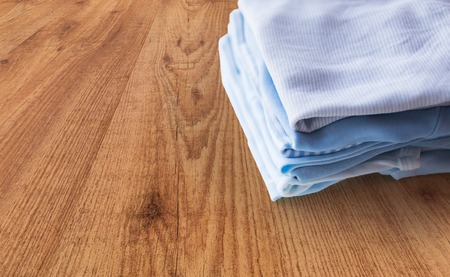 babyhood: clothing, babyhood, motherhood and object concept - close up of pile of baby clothes for newborn boy folded on wooden table