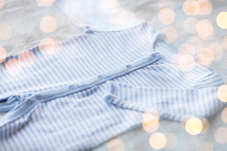 babyhood: baby clothes, babyhood, motherhood and object concept - close up of blue bodysuit on towel for newborn boy with holidays lights