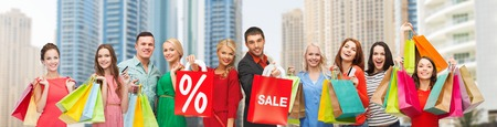 happy shopping: gesture, shopping and people concept - group of happy people with sale sign showing thumbs up Stock Photo