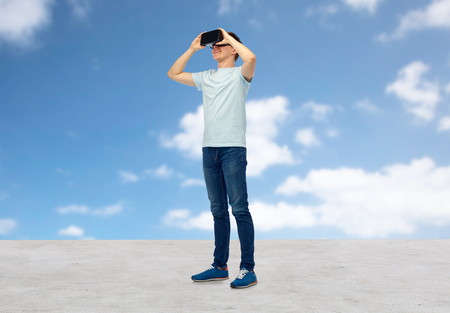 mediated: 3d technology, virtual reality, entertainment, cyberspace and people concept - happy young man with virtual reality headset or 3d glasses looking at something over blue sky and clouds background Stock Photo