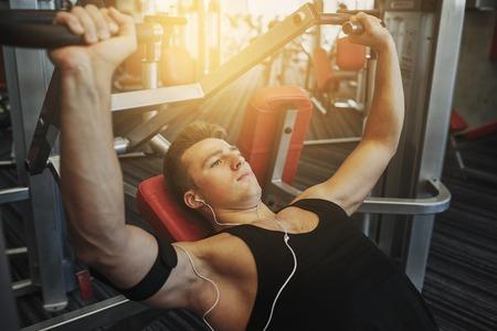 Sport, Ausrüstung, Technologie, Lifestyle und Menschen Konzept - junger Mann mit Kopfhörern Brustmuskeln auf Fitnessgerät beugen Standard-Bild