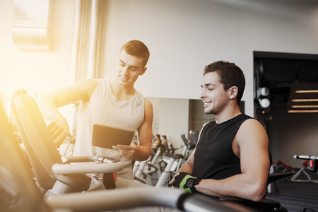 sport, fitness, equipment, technology and people concept - men with tablet pc computer exercising on gym machine Stock fotó