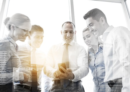 people watching: business, teamwork, people and technology concept - business team looking to smartphone in office Stock Photo