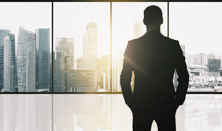 business and people concept - silhouette of businessman over office window and singapore city skyscrapers background and sun light