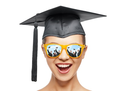 graduation, education, school and people concept - happy screaming teenage girl in shades and black mortarboard or bachelor hat over white background